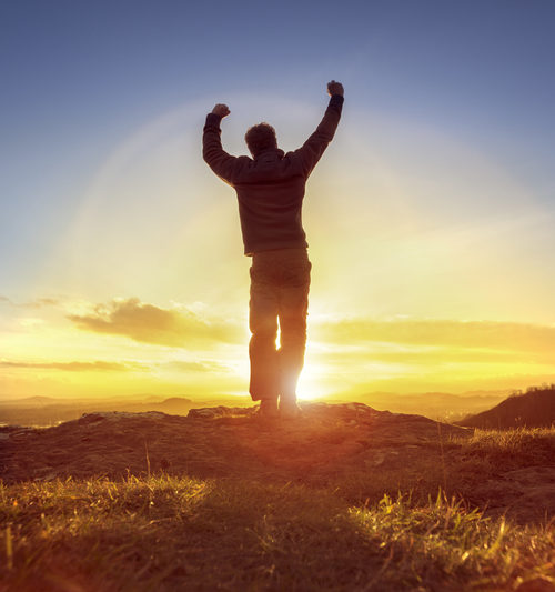 Happy man celebrating winning success or worship and praise against sunset